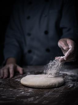 De hand die van de gebakjechef-kok witte bloem over ruw deeg op keukenlijst bestrooien.