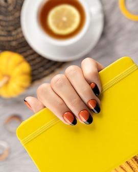 De hand die van de gemanicuurde vrouw gele blocnote op grijs houdt