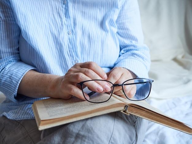De hand die van de hogere vrouw open boek en glazen houdt.