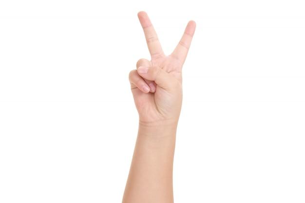 De hand die van de jongen het teken van overwinning en vredesclose-up toont.