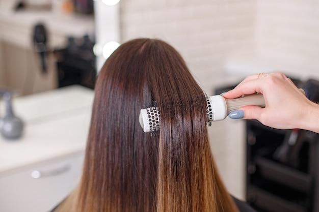De hand die van de kapper lang donkerbruin haar borstelen in de schoonheidssalon