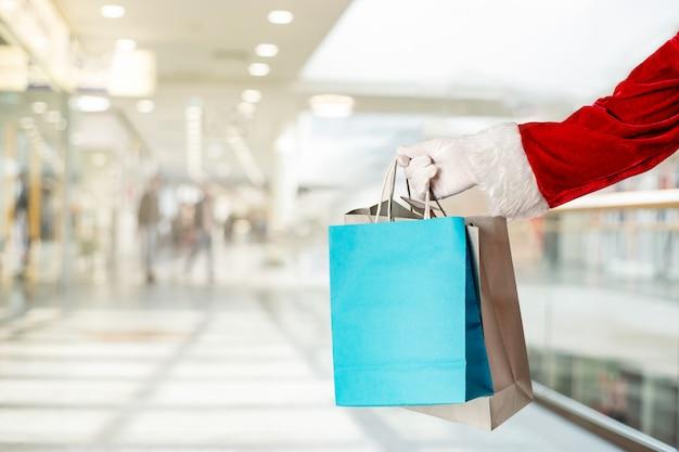 De hand die van de kerstman huidige papieren zakken in winkelcentrum houdt