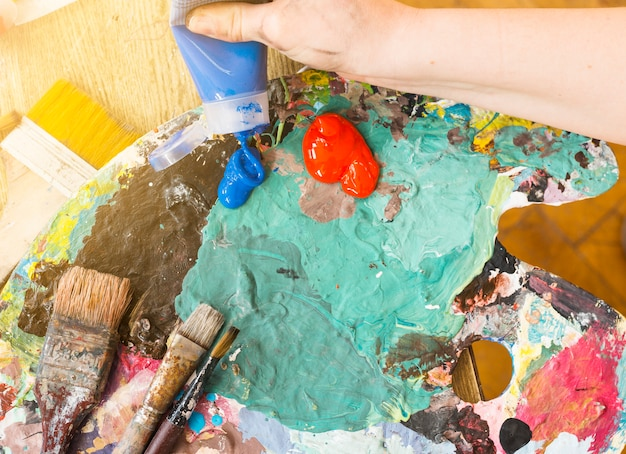 De hand die van de kunstenaar blauwe olieverfbuis op slordig palet drukt