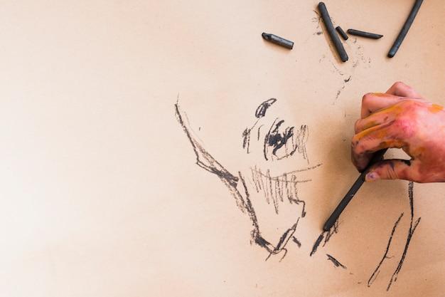 De hand die van de kunstenaar tekening met houtskool op papier schetst