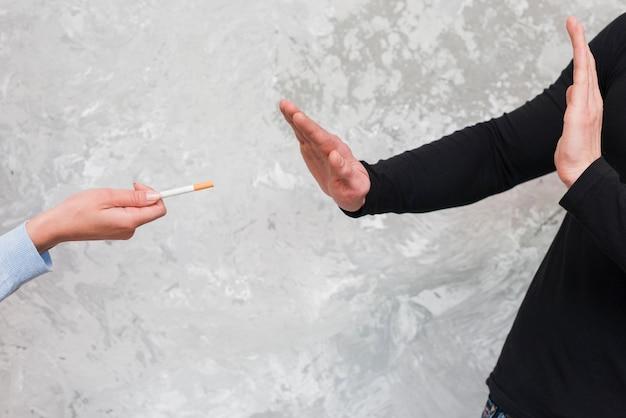 De hand die van de man sigaretaanbieding door vrouw verwerpt
