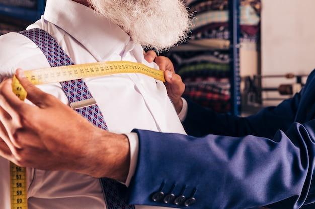 De hand die van de manierontwerper van de borst van zijn klant met gele metende band meten