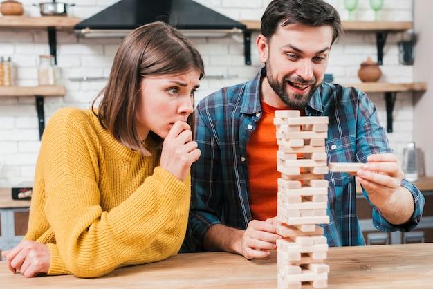 De hand die van de mens een blok aan een onstabiele en onvolledige toren van houten blokken neemt of zet