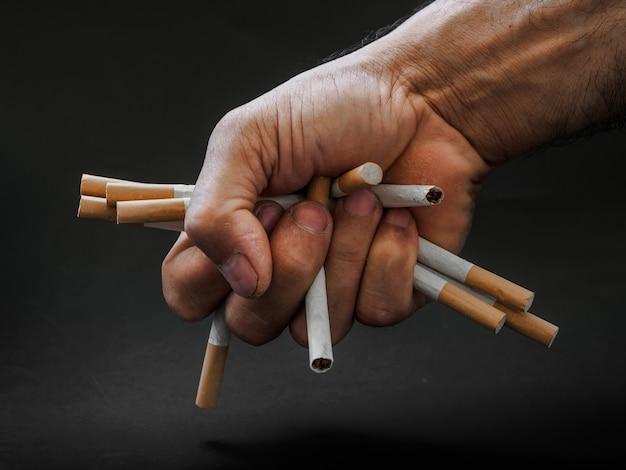 De hand die van de mens en sigaretten op zwarte achtergrond houdt vernietigt