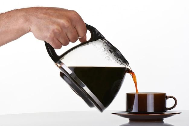 De hand die van de mens koffie in een bruine kop houdt en giet