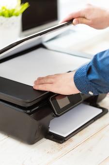 De hand die van de mens kopieën maakt. werken met de printer