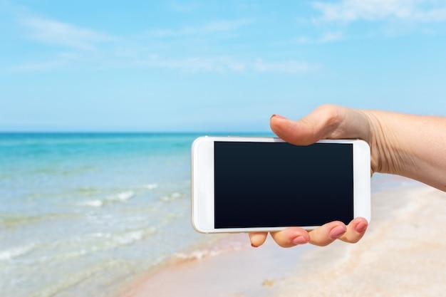 De hand die van de mooie vrouw slimme telefoon met behulp van bij strand