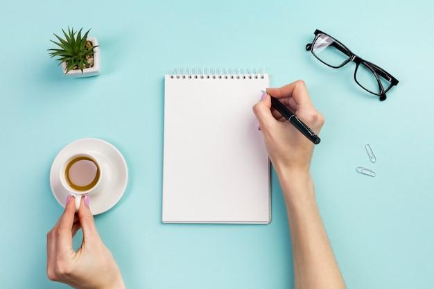 De hand die van de onderneemster op blocnote met pen schrijft en koffiekop over het bureau houdt