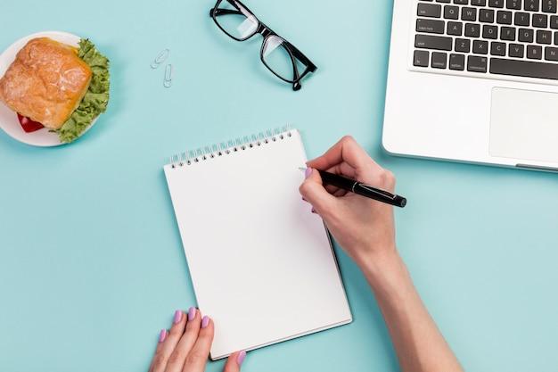De hand die van de onderneemster op de spiraalvormige blocnote met pen over het bureau schrijft