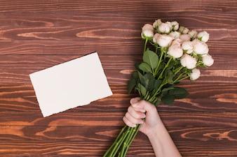 De hand die van de persoon bos van witte rozen houdt; blanco papier over houten bureau