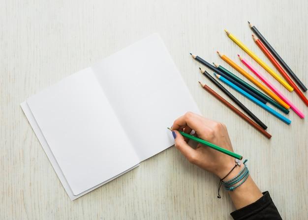 De hand die van de persoon op leeg wit boek schrijft dat kleurenpotlood gebruikt