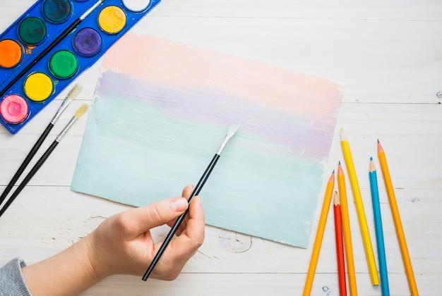 De hand die van de persoon op papier met verfborstel en waterverf over bureau schildert