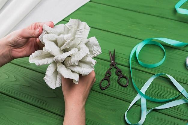 De hand die van de persoon valse crêpepapierbloem op groene geweven achtergrond houdt
