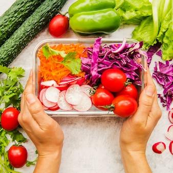 De hand die van de persoon verse groenten en ingrediënten voor salade in container houdt