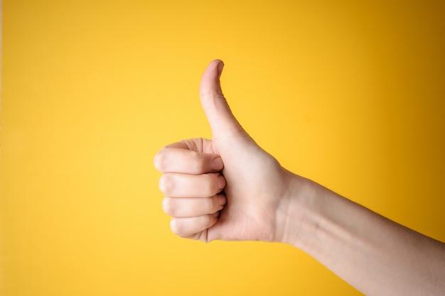 De hand die van de schalie duimen op gebaar toont