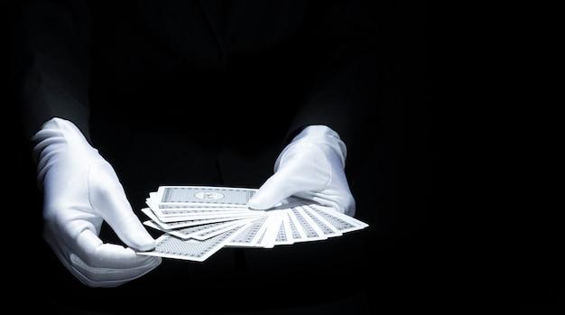 De hand die van de tovenaar kaart van gewaaid dek van speelkaart selecteert tegen zwarte achtergrond