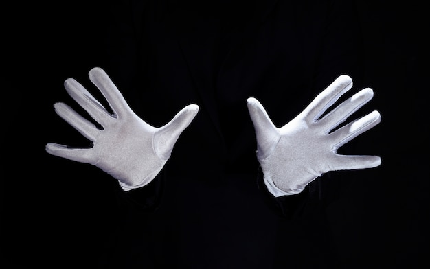 De hand die van de tovenaar witte handschoenen draagt tegen zwarte achtergrond