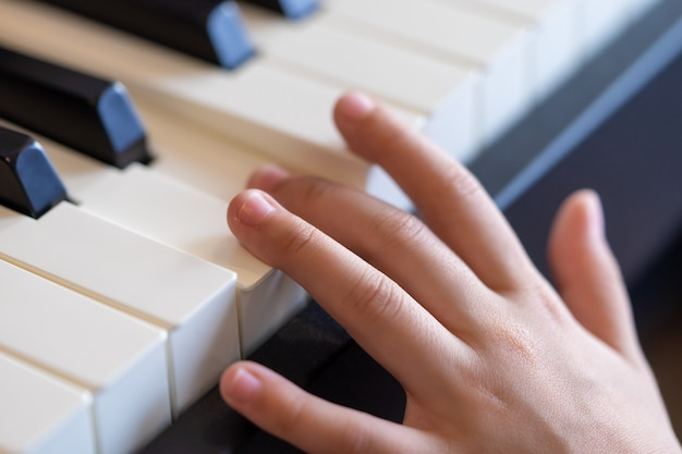 De hand die van de uitvoerende macht van de jonge muziek de piano speelt