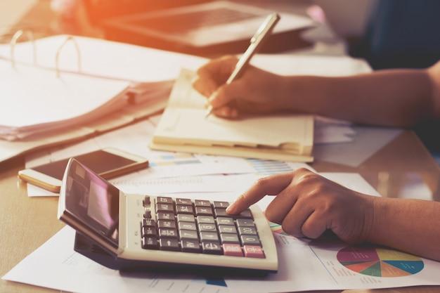 De hand die van de vrouw calculator gebruikt en schrijft maakt nota met berekent