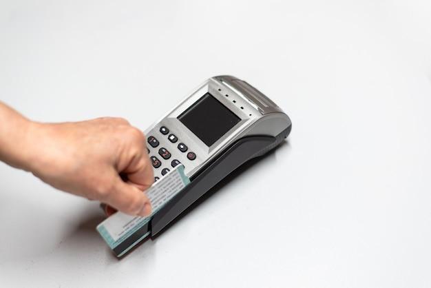De hand die van de vrouw creditcard door een datafoon overgaat, kaartlezer om in tijd van verkoop ten laste te nemen.