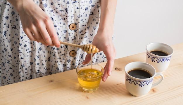 De hand die van de vrouw de honing in glas met kop theekoppen op houten bureau druipt