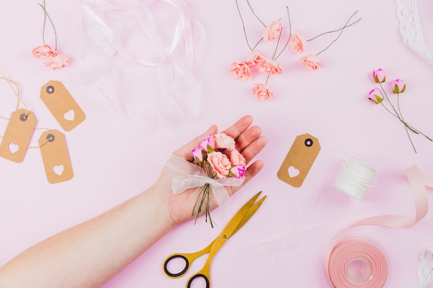 De hand die van de vrouw de kunstbloemen met lint op roze achtergrond toont