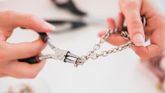 De hand die van de vrouw de metaalhaak met buigtang bevestigt