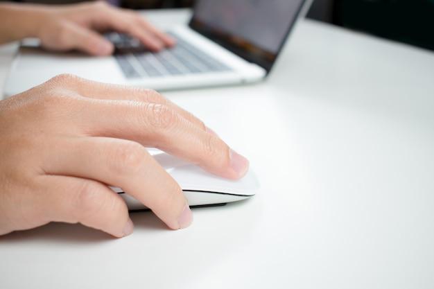 De hand die van de vrouw de muis houdt terwijl het werken aan een computer.