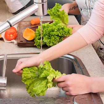 De hand die van de vrouw de sla in de keukengootsteen wast