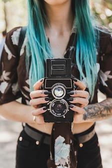De hand die van de vrouw de tweelinglens reflex oude fotocamera houdt