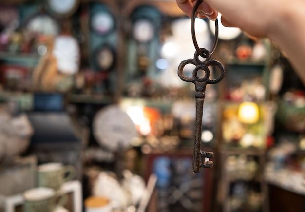 De hand die van de vrouw een antieke sleutel houdt