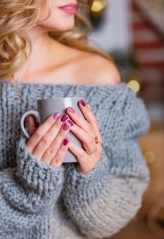 De hand die van de vrouw een kop thee houdt