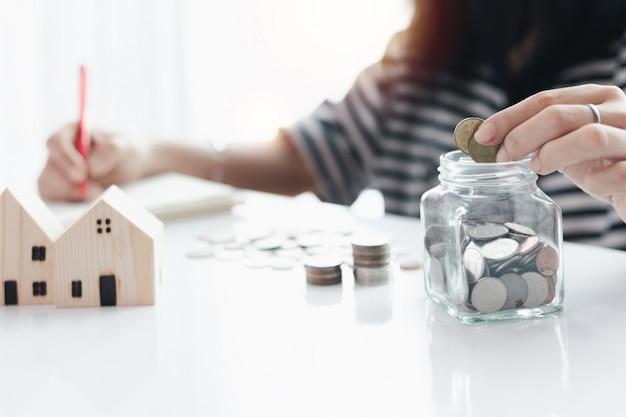 De hand die van de vrouw een muntstuk bespaart in de glaskruik voor planning, huisvesting en bezit financieel concept