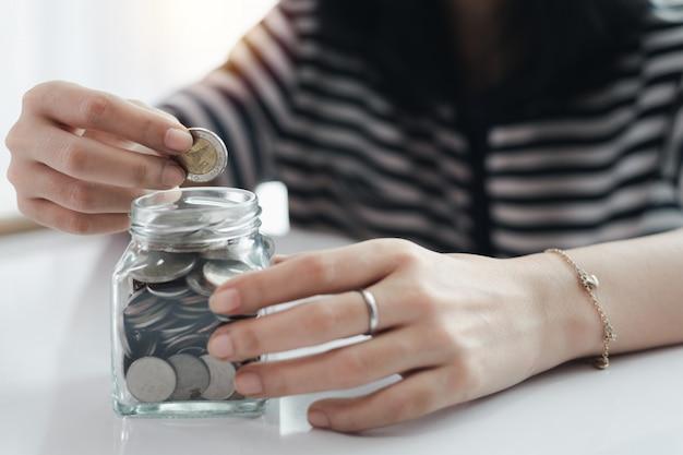 De hand die van de vrouw een muntstuk voor planning, huisvesting en bezits financieel concept bewaart