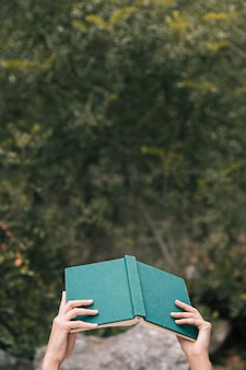 De hand die van de vrouw een open boek houdt tegen groene bomen in hand