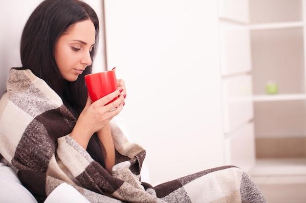 De hand die van de vrouw een rode kop van koffie houdt. met een mooie wintermanicure. drinken, mode, ochtend