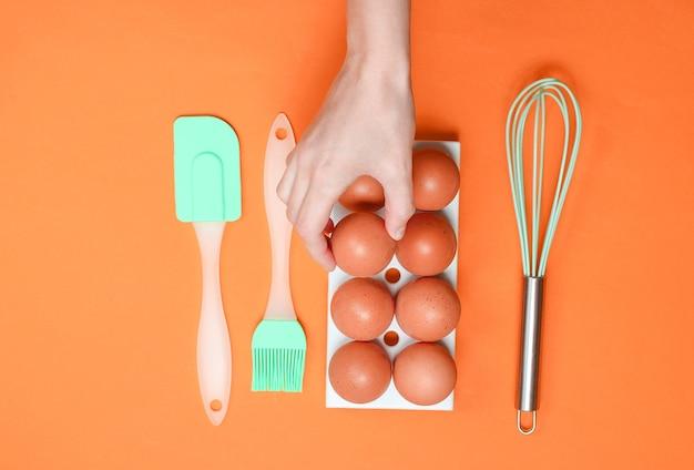 De hand die van de vrouw ei neemt van het culinaire concept van het eierblad