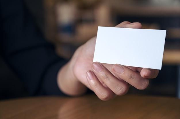 De hand die van de vrouw en een leeg adreskaartje op lijst in bureau houdt toont