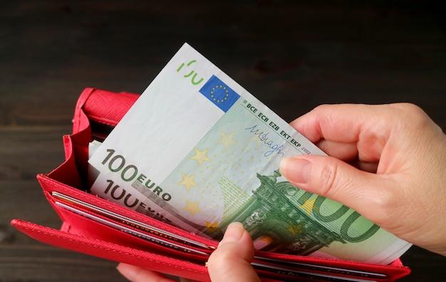 De hand die van de vrouw euro bankbiljetten van de rode portefeuille neemt