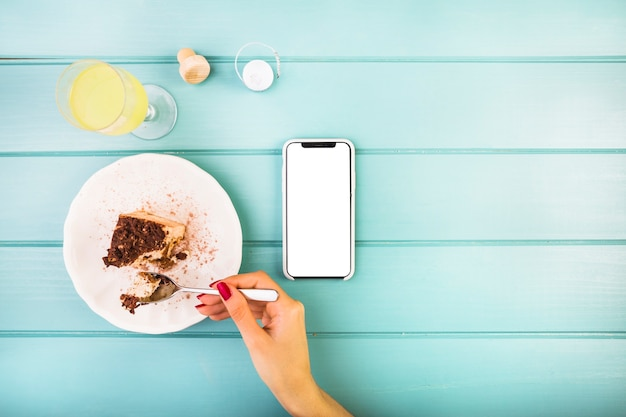 De hand die van de vrouw gebakje met drank en cellphone op lijst eet