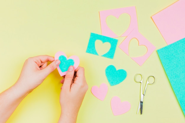 De hand die van de vrouw hartvorm met blauw en roze document op gele achtergrond maakt