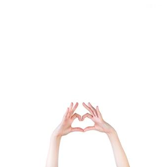 De hand die van de vrouw hartvorm over witte achtergrond vormt
