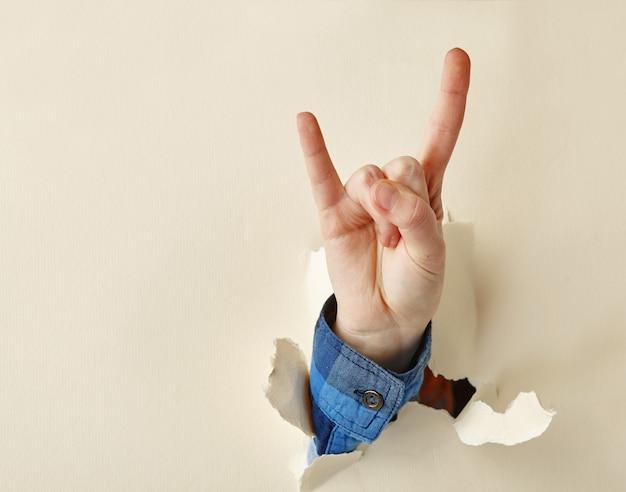 De hand die van de vrouw het gebaar van de rots toont, breekt door de muur van het witboek