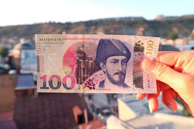 De hand die van de vrouw het georgische bankbiljet van 100 lari met de onscherpe luchtmening van tbilisi op achtergrond houden