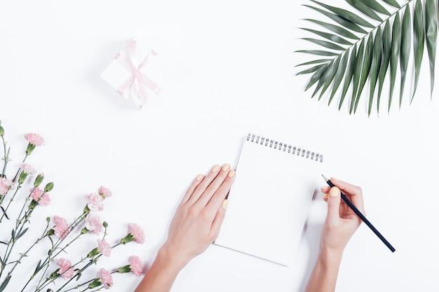 De hand die van de vrouw in een notitieboekje bij het bureau, hoogste mening schrijven