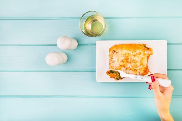 De hand die van de vrouw lasagne op houten achtergrond eet